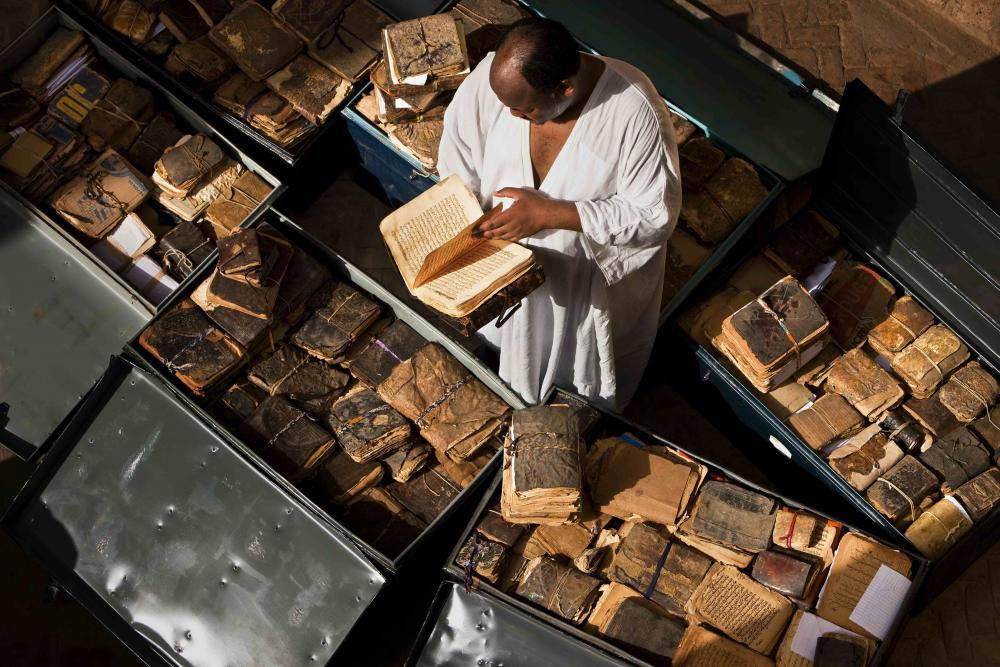 Abdel Kader Haïdara, a librarian who smuggled hundreds of thousands of manuscripts from jihadist-occupied Timbuktu to safety in Bamako, stands with ancient volumes from Timbuktu packed into metal trunks. Photo: Brent Stirton/Getty Images.