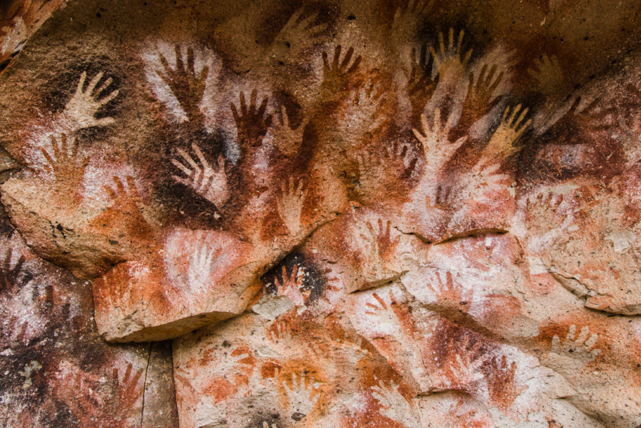 Hand stencils dating from 5,000–7,000 BCE photographed on the Cueva de las Manos, Santa Cruz, Argentina by Javier Etcheverry, 2015. Courtesy: Javier Etcheverry